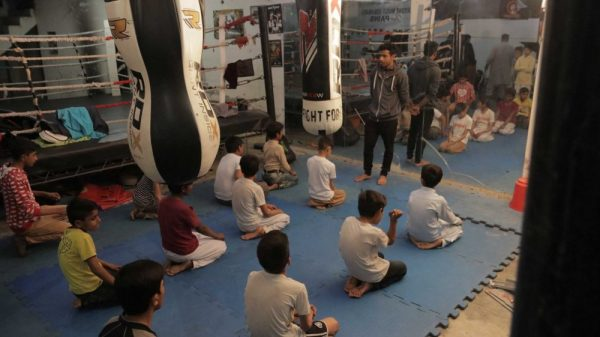 Coach Irfan lines up the kids for a pep talk before class.